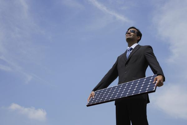 PictureIndia - Businessman holding solar panel.