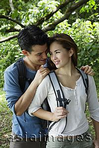 Asia Images Group - Couple with back packs standing under a tree