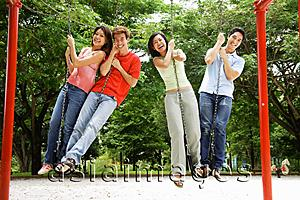 Asia Images Group - Young adults in playground, standing on swings, looking at camera