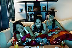 Asia Images Group - Three young women in living room, playing video games