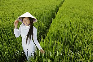 Asia Images Group - Young woman wearing traditional Vietnamese outfit standing in rice paddy