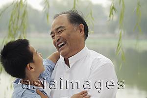 Asia Images Group - Head shot of grandfather and young boy smiling at each other