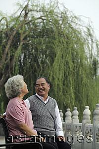 Asia Images Group - Older couple looking at each other and laughing in a park