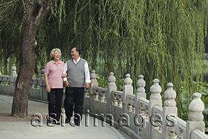 Asia Images Group - Older couple walking by a lake, smiling at each other