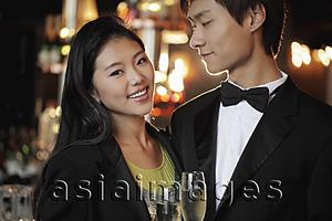 Asia Images Group - Young couple dressed up at night holding champagne glasses