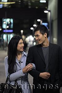 Asia Images Group - Young couple walking together on the street at night