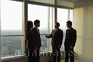 Asia Images Group - Businesspeople talking in front of a window in an office