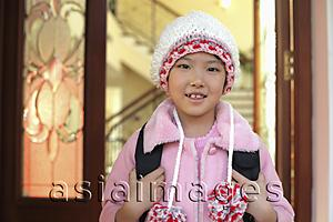 Asia Images Group - Young girl leaving her home in knitted cap and pink coat