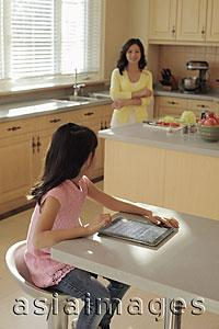 Asia Images Group - Mother watching her daughter play on a digital tablet as she cooks